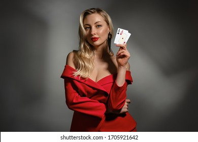 Blonde model in red dress and black earrings. She is showing two aces, posing on gray studio background. Poker, casino. Close-up, copy space