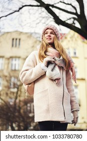 Blonde model in urban background with sun backlight. Young girl wearing winter coat and scarf standing in the street. Pretty female with straight hair hairstyle
