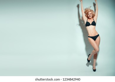Blonde model wearing black underwear with smile and playful standing against light background with copyspace