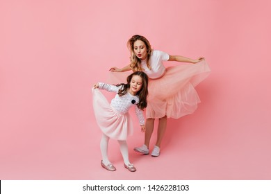 Blonde mom and curly daughter in lush skirts bow like princesses on pink background
