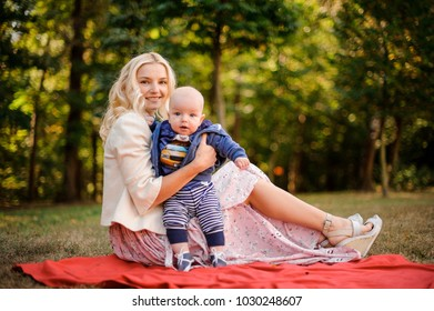 Blonde mother with a baby son sitting on the blanket in a beautiful autumn park