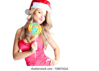 Blonde with a multicolored candy in her hands is wearing a Santa Claus hat