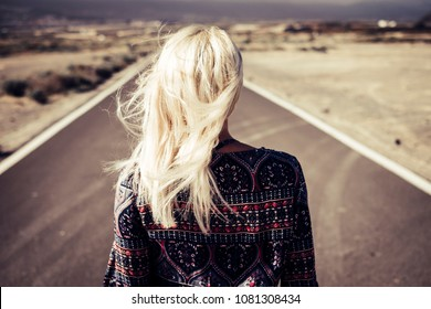 blonde nice girl walk and go on on a long straight road outdoor to discover and live her life at top. wind in the hair, freedom and decision concept to follow dreams and projects strongly
