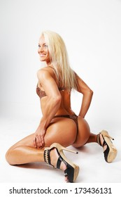 Blonde on high heels sits and smiles