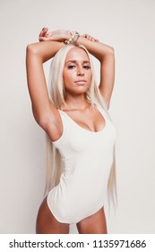 Blonde on a white background.Sexy blonde.Girl on a white background in a white bodysuit