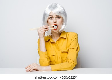 blonde in an orange shirt red lips for white table holding sushi with chopsticks...