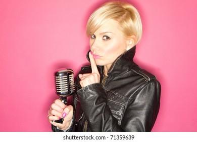 blonde pop star on pink background singing , holding retro mic