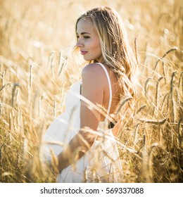 Blonde pregnant woman stands in high grass of wheat field