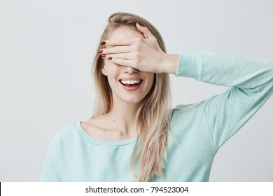 Blonde pretty girl closing her eyes with hand, having happy expression, smiling broadly, anticipating to recieve present from her boyfriend. Fair-haired young woman waiting for pleasant surprise