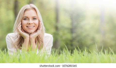 Blonde pretty girl laying on the grass in spring park and smiling
