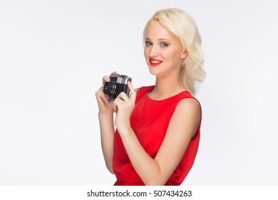blonde in a red dress on a white background with a camera