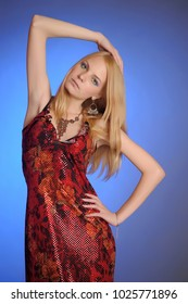 Blonde in red evening dresses blue background