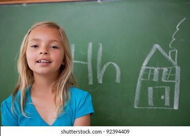Blonde schoolgirl posing in front of a blackboard in a classroom
