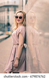 Blonde sensual and attractive woman with awesome look, using seductive body language. Fashion outfit pink dress, sunglasses elegant golden watch street fashion urban sun light summer afternoon sunset