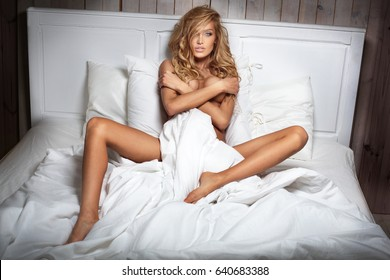 Blonde sensual caucasian woman posing in bedroom.