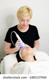 Blonde serious beautician applying blue led light therapy to female customer in beauty salon, facial photo therapy for skin pore cleansing. Anti-aging treatments and photo rejuvenation procedure