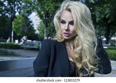Blonde sexy beauty posing on bench