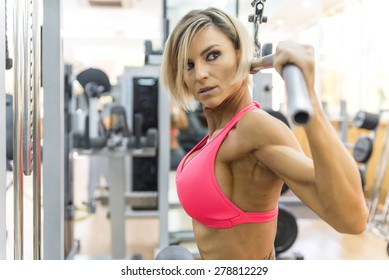 Blonde sexy bodybuilder pulldown practice in gym, back exercise