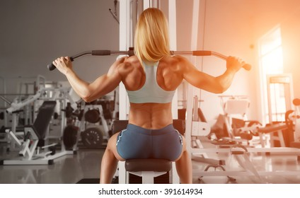 Blonde sexy fitness woman in sport wear with perfect body in the gym posing before training set. Attractive fitness woman, trained female body. Fitness woman in the gym. Bodybuilder woman in the gym.