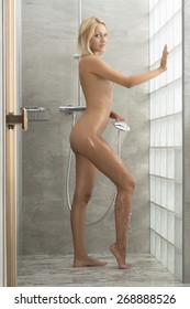 Blonde sexy woman in the bathroom. She is under the shower and she is splashing her body with water. Perfect naked body