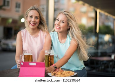 Blonde sister woman drinking beer in bar smiling and toatsing jar