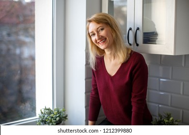 Blonde is sitting in the kitchen by the window and smiling