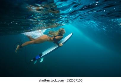 0b530fd09612a A blonde slim girl doing duck dive under blue wave. Water ripples under  ocean surface