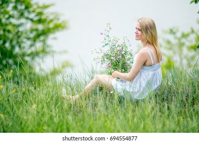 Blonde slim girl in white dress sits on the grass and holds bouquet of wild pink flowers.