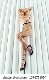 Blonde slim woman, dressed only in sexy black fishnet tights and high heels, keeping her breasts and lying on white pillars background.