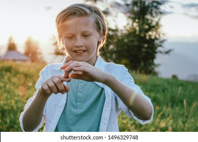 Blonde smiling boy holds a grasshopper in his hand at the sunset meadow, rural scene