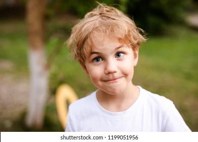 Blonde smiling boy with strabismus in warm park
