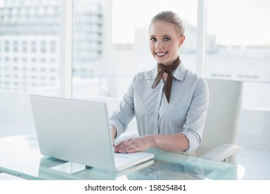 Blonde smiling businesswoman using laptop in bright office