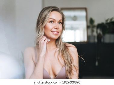 Blonde smiling woman 35 year plus clean fresh face and hands with long hair does facial massage with gouache scraper in underwear