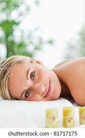 Blonde smiling woman relaxing on massage lounger in a wellness center