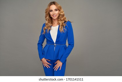 Blonde smiling woman in smart business attire over gray background