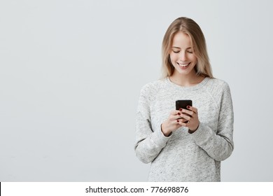 Blonde smiling young woman demonstrating white teeth using cell phone, messaging, being happy to text with her boyfriend, looking at screen of smartphone. Modern technologies and communication