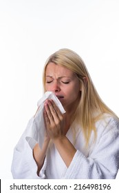 Blonde sneezes into a handkerchief