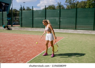 A blonde sportive woman tennis player gets prepared to make a strong overhand serve over the net