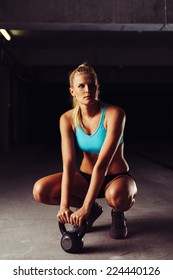 Blonde sportswoman crouching with a kettlebell in her hands