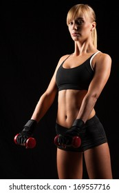 blonde sporty woman holding red dumbbells in the dark