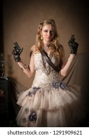 Blonde steampunk woman in strapless couture dress with belt, posing with a gun in each gloved hand.