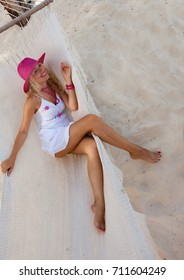 The blonde in a straw hat lies in a hammock