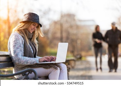 Blonde student girl with hat on park bench working on laptop