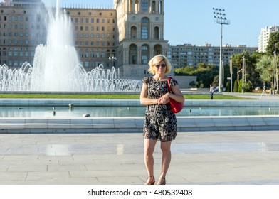 The blonde in sunglasses on the background of the fountain. The building of the government of Azerbaijan. Freedom Square. Baku