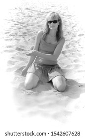 blonde in sunglasses pours sand from her hands