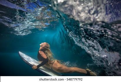 6ff4868c3b Blonde surfer in bikini with surf board dive under ocean wave lip.  Underwater sport activity