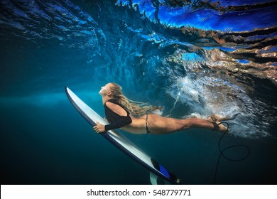 Blonde surfer girl in bikini with board dive under big ocean wave lip. Underwater sport activity with fun. Family lifestyle, water sport lessons and beach swimming activity on summer vacation