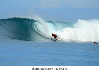 Blonde surfer in orange shirt on big wave, Mentawai Islands, Indonesia