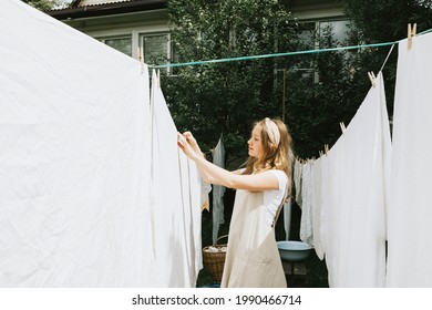 blonde teen girl in linen apron is doing homework washing clothes in basin and hanging them on ropes on the street in courtyard of village cottage house, concept of summer and freshness, laundry day