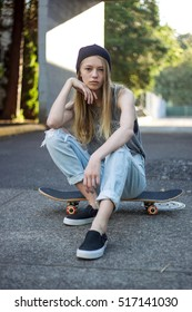 Blonde teen girl wearing tank and jeans with skateboard on street.